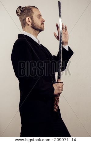 Young Businessman Samurai In A Black Suit With A Japanese Sword