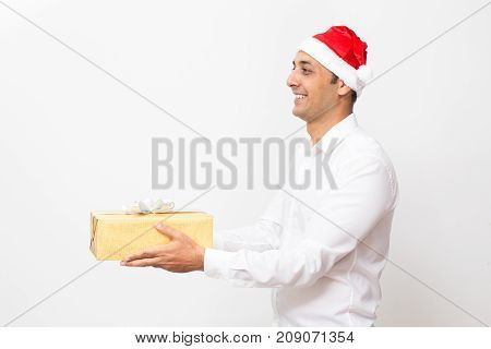 Smiling man giving Christmas gift to colleague congratulating with New Year. Cheerful handsome office worker enjoying gift-giving time. Holiday concept
