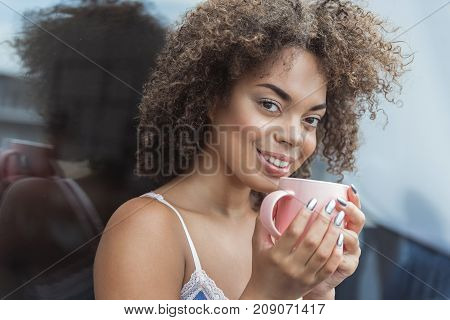 Portrait of beaming mulatto girl drinking cup of delicious beverage in morning. She looking at camera