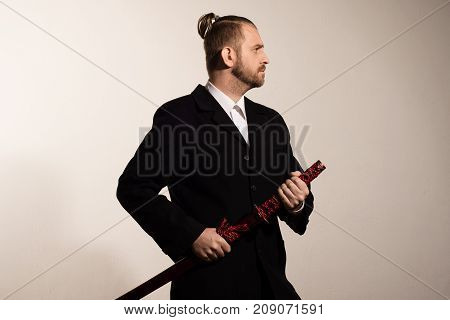 Attractive Businessman In A Black Suit Gets A Samurai Sword
