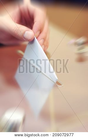 Image of a ballot box and hand putting a blank ballot insideelections voting concept