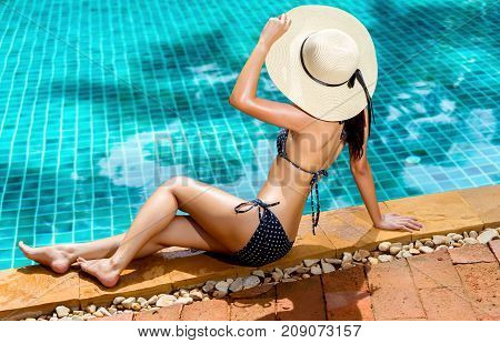 Bikini woman sexy in pool relaxing young asian beautiful female resting in vacation on summer season with hat at resort swimming pool edge