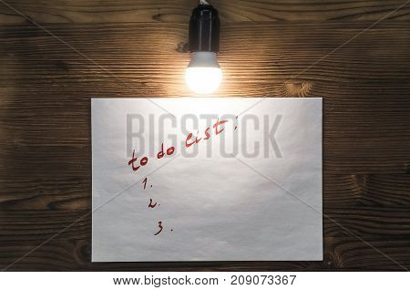 To do list paper page on the wooden desk table surface in the light of bulb lamp with copy space. To do list.