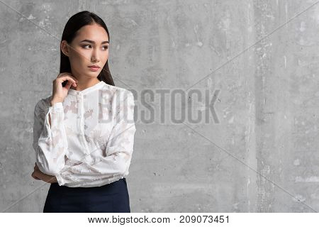 Portrait of serene young asian businesswoman locating indoor. Profession concept. Copy space
