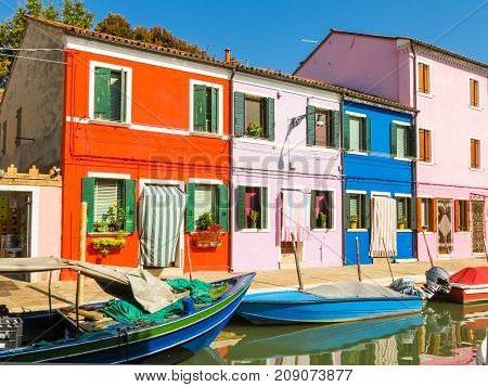 Burano Island, colorful houses and boats on channels of island. Venice, Italy