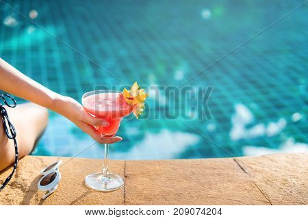 Bikini woman in pool relaxing with cocktail sunglasses young asian beautiful sexy female resting in vacation on summer season with hat at resort swimming pool