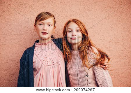 Portrait of two pretty little preteen girls wearing knitted pullover and jacket friends playing together outside. Fashion for teens. Kneatwear