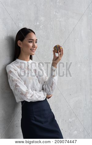Side view smiling businesswoman looking at sphere while leaning against wall. Copy space. Inspiration concept