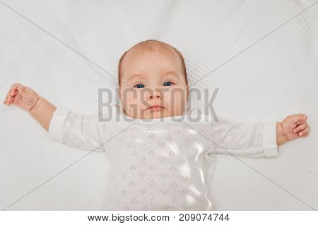 Adorable baby girl lying on white blanket and smiling wearing heart body.