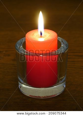 A burning candle in the glass candle holder