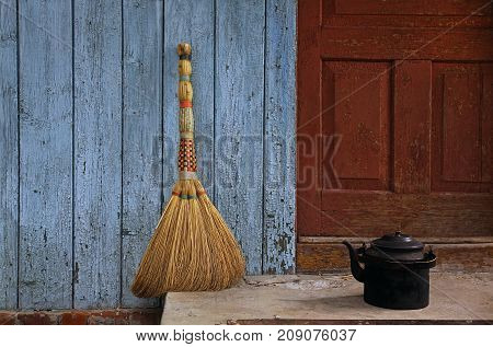 Broom and old teapot on the background of an irritated paint of a wall and a door