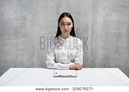 Portrait of serene asian woman sitting at table. Clipboard with document locating on it. Job concept. Copy space