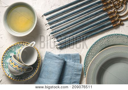Hanukkah with candles, plates, butter in a bowl and blue napkin horizontal