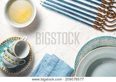 Chanukiah frame, butter in a bowl, plates and cups horizontal