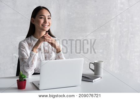 Glad woman is locating at workplace and looking ahead with sweet smile. Portrait. Copy space on right side