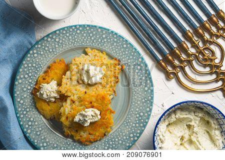 Latkes and curd cheese on a plate and on a blue napkin, chanukia horizontal