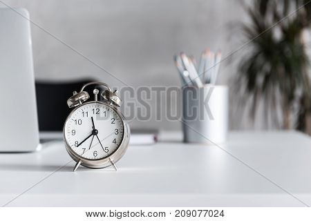 Alarm clock is locating on countertop of desk in office. Close up of watch. Copy space on right side