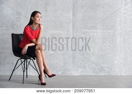 Cheerful woman is sitting on chair and looking ahead dreamy smile. Portrait. Copy space on right side