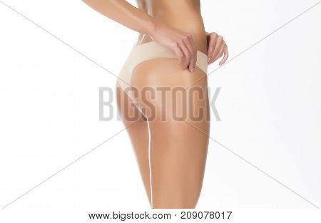 Perfect clean skin with no cellulite over white background. Beige thongs.