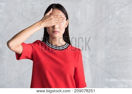 Asian woman is locating near wall and covering eyes with palm. Waist up portrait. copy space on right side