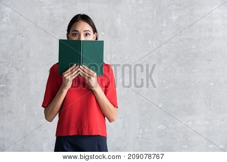Feeling scared. Frightened young asian woman is holding book and covering her face with it. She is standing and looking at camera with shock. copy space in the right side