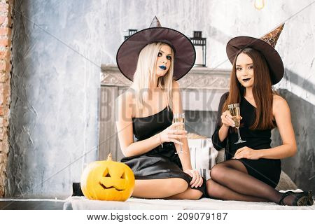 Two Happy Young Women In Black Witch Halloween Costumes On Party Sitting On Bed