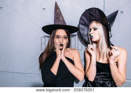 Portrait Of Two Happy Young Women In Black Witch Halloween Costumes On Party