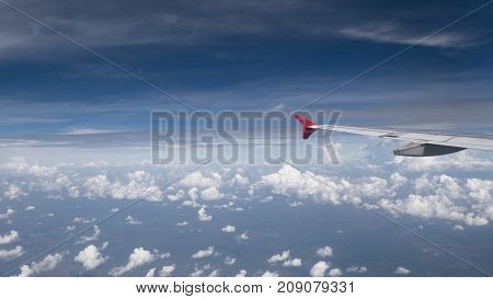 Plane travel concept : View from aircraft window. Clouds and blue sky under airplane wing as seen through window of an airplane in wide angel with copy space for travel agency background