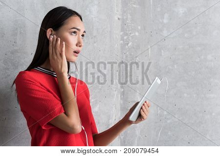 Communication problems. Grieved young asian woman in earphones is holding tablet and touching ear while looking aside sadly. Copy space in the right side
