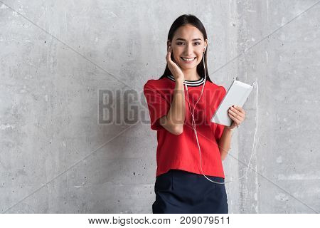 Positive attitude. Portrait of cheerful charming girl is standing with tablet and touching her ear while looking at camera with smile. Copy space in the left side