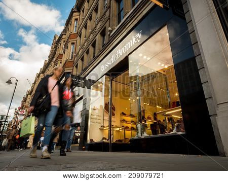 LONDON UK - 5 OCTOBER 2017: Low and wide angle view of the facade to the popular high street Russell & Bromley shoe and bag shop in London's Knightsbridge district with shoppers walking by.