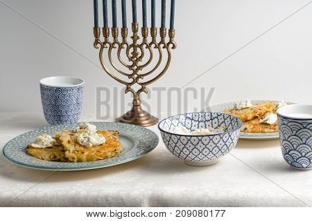 Latkes on a plate, Hanukkah, cups with milk on a white tablecloth horizontal