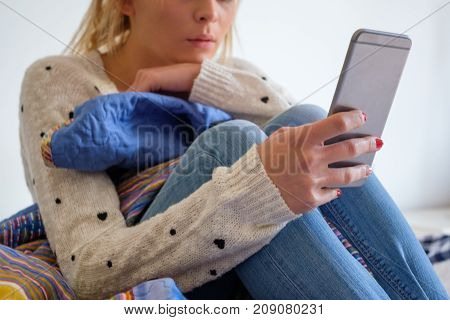 Young Teenage Girll With Phone On Her Bed