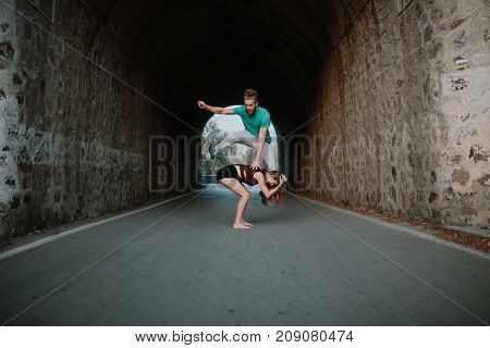 Couple playing leapfrog jumping in a tunnel