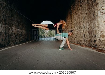 Young couple performing breakdance on a road.