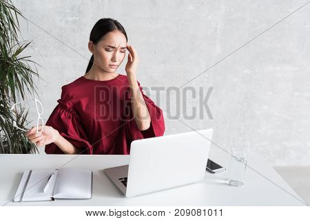 Malaise. Portrait of Asian businesswoman is sitting at table with laptop and having terrible headache. She is touching her head and expressing pain while contracting her brow with closed eyes. Copy space