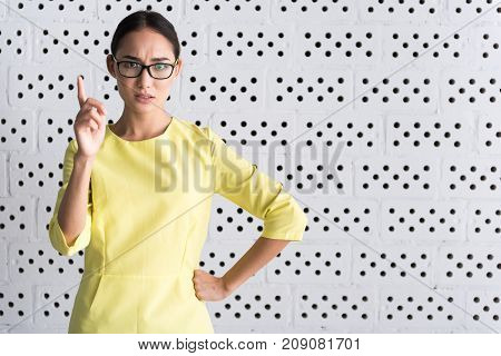 My opinion. Waist up portrait of convincing annoyed girl is pointing thumb up and frowning her forehead while standing against white wall. Copy space in the right side