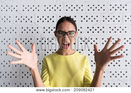 Full of anger. Portrait of annoyed young woman in glasses is looking at camera with fury and shouting while gesticulating madly. She is standing against brick wall background