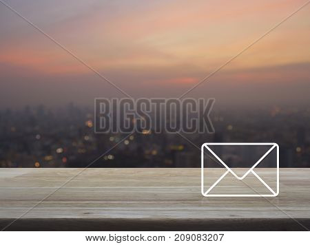 Mail icon on wooden table over blur of cityscape on warm light sundown Contact us concept