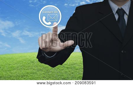 Businessman pressing telephone and mail icon button over green grass field with blue sky Contact us concept