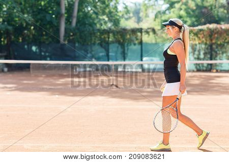 Full body photo of blonde female tennis player in action with racket in a tennis court outdoor. Woman tennis player dressed white skirt, black T-shirt and black cap