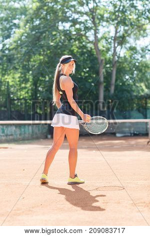 Full body portrait of blonde young female tennis player in action with racket in a tennis court outdoor. Woman tennis player dressed white skirt, black T-shirt and black cap