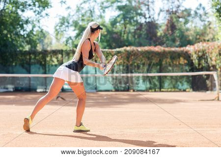 Full body portrait of white blonde female tennis player in action in a tennis court outdoor. Photo of the girl is made from the back. White woman tennis player dressed white skirt, black T-shirt and black cap