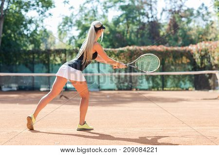 Full body portrait of white blonde girl tennis player in action in a tennis court outdoor. Photo of the girl is made from the back. White woman tennis player dressed white shorts, black T-shirt and black cap