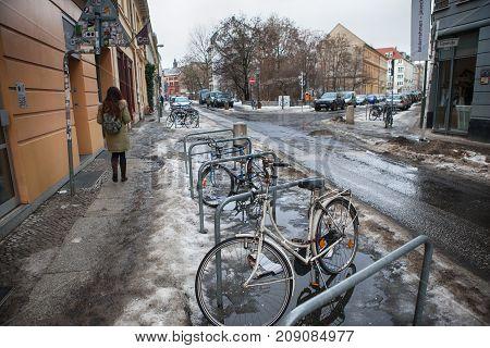 BERLIN, GERMANY - 7 JAN 2011 : German people stop and lock bike at bicycle parking beside road.