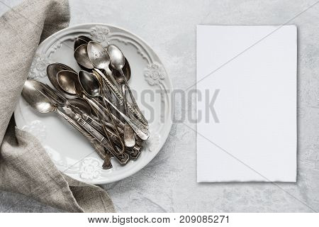 Various silverware on a ceramic plate and white blanc paper card on the background of gray concrete surface with copy-space