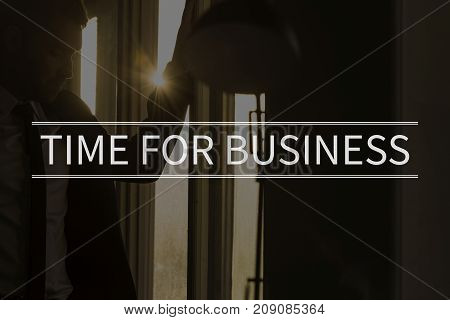 Time for business text over conceptual business scene with businessman in a dark office with sunburst entering the window.
