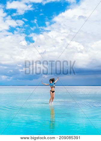 Cheerful bright brunette girl jumps on the water for a photo. A heavenly place, beautiful seascape, clouds on the horizon. Girl in swimsuit makes a jump on salty water of saline.