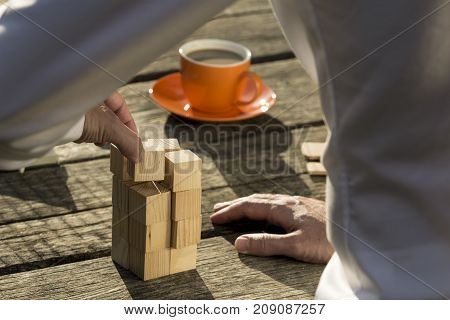 Man Building A Construction From Toy Blocks