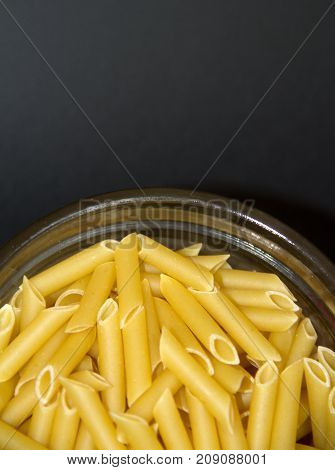 Composition of raw macaroni on a color background